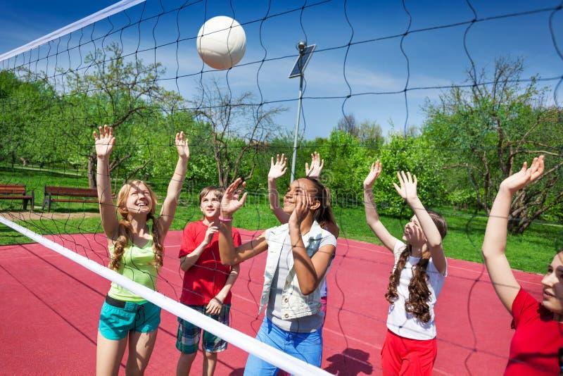 Delle ragazze del gioco pallavolo insieme sul campo da giuoco fotografie stock