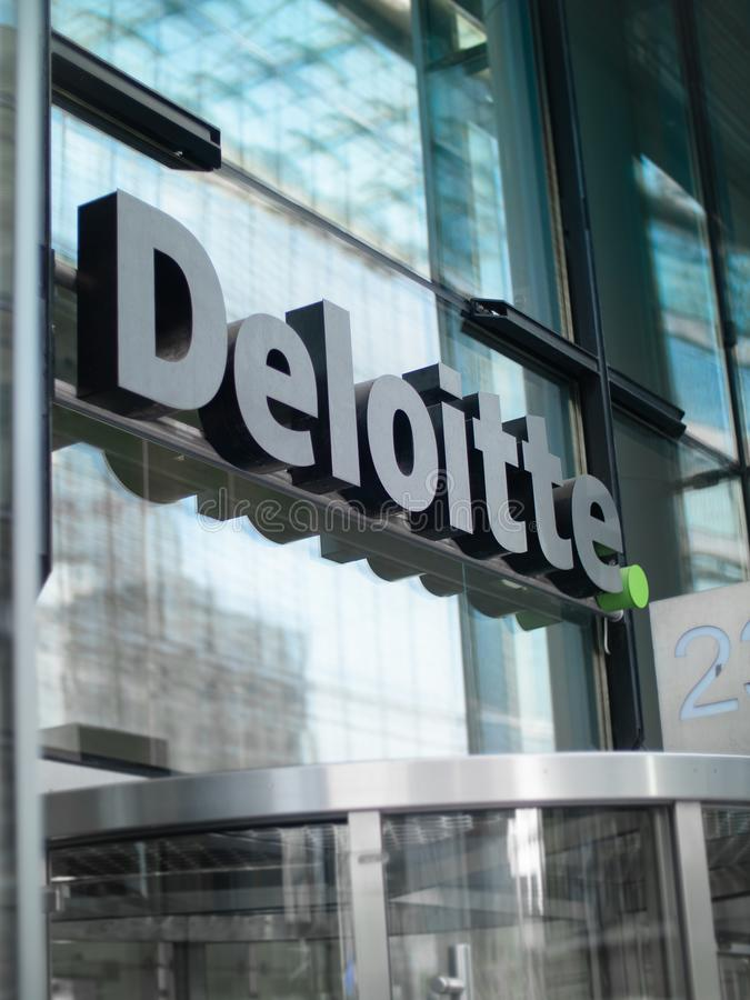 The Deloitte offices signage over the front door to their Berlin Building. BERLIN, GERMANY - JULY 2018: The Deloitte offices signage over the front door to their royalty free stock photos