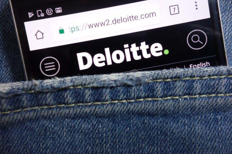 Deloitte website displayed on smartphone hidden in jeans pocket royalty free stock images
