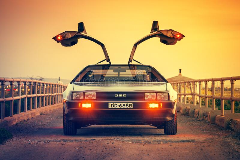 DeLorean DMC-12 car fron view. Adelaide, Australia - September 7, 2013: DeLorean DMC-12 car front view with opened gull-wing doors parked on the bridge at dusk royalty free stock images