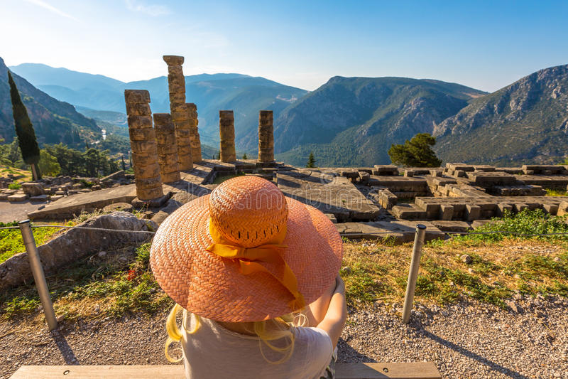 Delphi Temple of Apollo. A young tourist with a orange wide-brimmed hat contemplates the columns of the Temple of Apollo in the Archaeological Site of Delphi royalty free stock photography