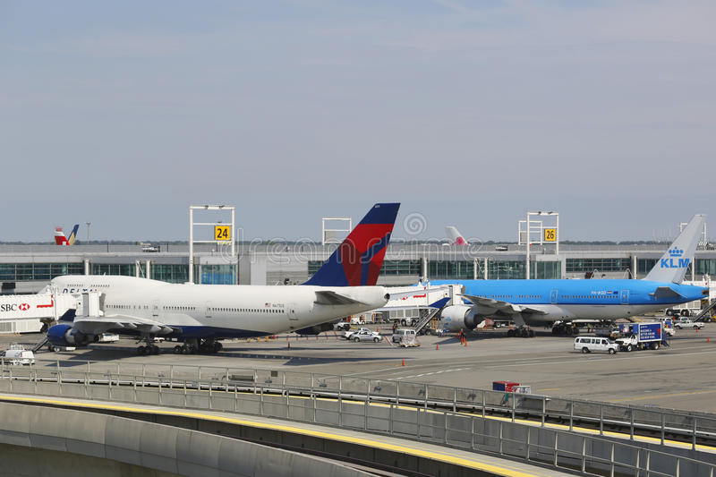 Delta Airline Boeing 747 and KLM Boeing 777 at the gates at the Terminal 4 at John F Kennedy International Airport in New York. NEW YORK- JULY 10: Delta Airline royalty free stock photos