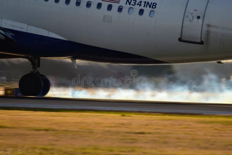 Delta Airlines-vliegtuig die op een baan met bandrook landen stock foto