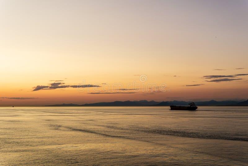 DELTA, Canada - 12 JUILLET 2019 : cargo au coucher du soleil nuageux dans le détroit de la Géorgie images libres de droits