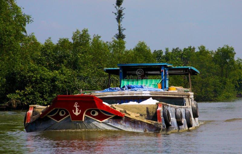 DELTA DE MEKONG, VIETNAME: 30 DE DEZEMBRO 2014: Barco sobrecarregado do estilo da sampana com os olhos de curva estilizados típic fotos de stock royalty free