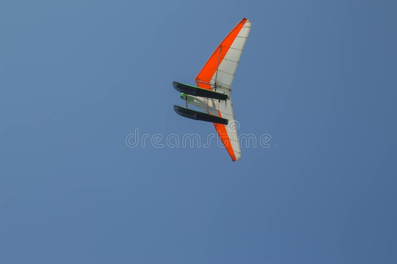 Delta wing with engine flies by the blue sky. Motorised hang glider. Delta wing with engine flies by the blue sky royalty free stock photography