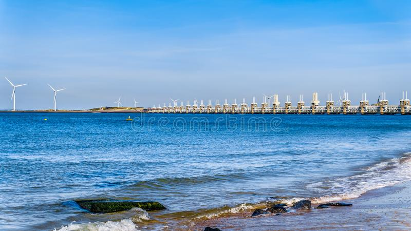 The Delta Works Storm Surge Barrier and Wind Turbines at the Oosterschelde viewed from Banjaardstrand. The Delta Works Storm Surge Barrier and Wind Turbines at royalty free stock image