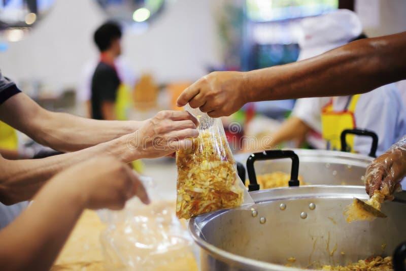 Deltagande, i att dela mat för det fattigt: begreppet av hungersnöd i världen royaltyfri foto