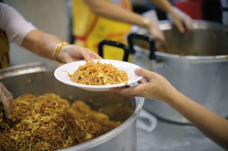 Deltagande, i att dela mat för det fattigt: begreppet av hungersnöd i världen royaltyfri bild