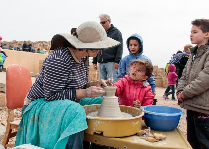 Deltagare av festivalen undervisar flickan att göra kannan av lera royaltyfri foto