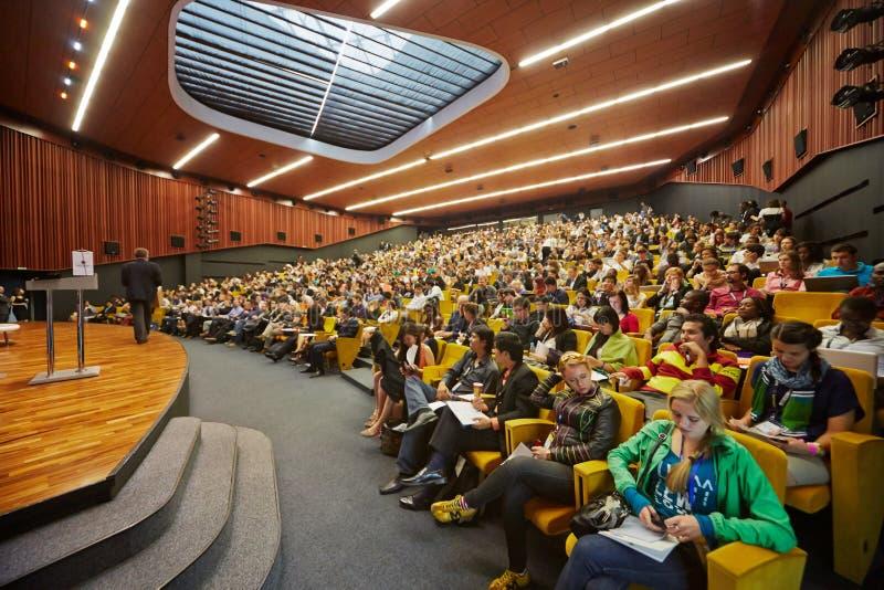 Deltagare av global ungdom till affärsforum i kongress-korridor royaltyfri bild