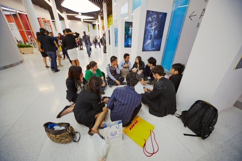 Deltagare av global ungdom till affärsforum sitter i lobby royaltyfria bilder