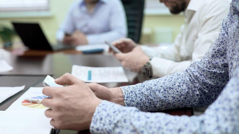 Deltagare för fungerande möte som försöker ny online-tjänst för företag på mobiltelefoner royaltyfri fotografi
