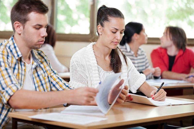 Deltagare som fungerar i klassrum arkivfoton
