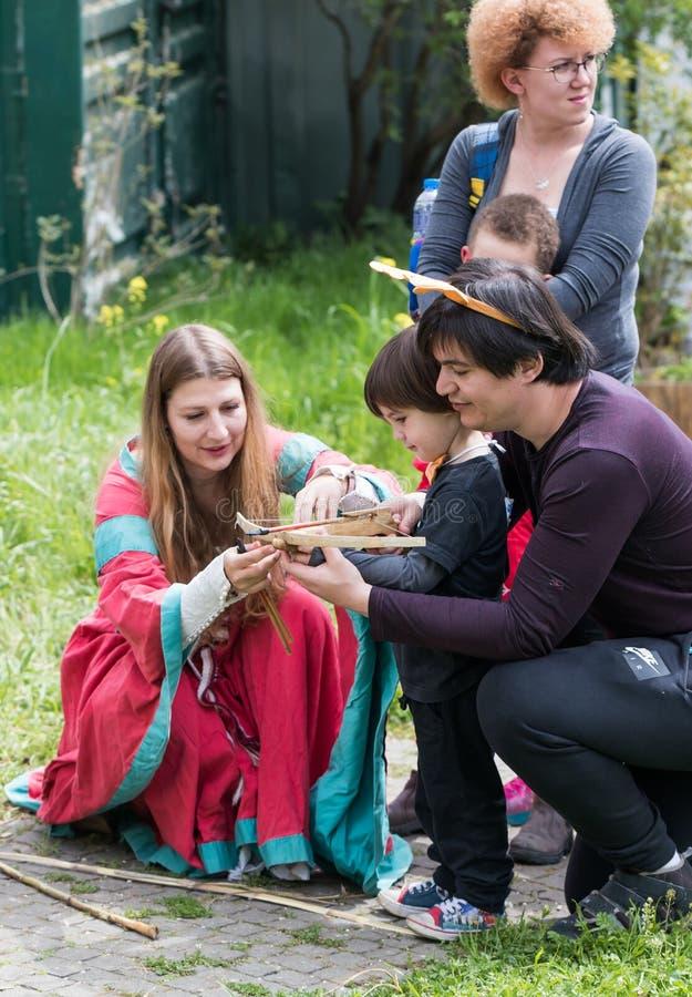 Deltagaren av den iklädda festivalen en medeltida townwomandräkt hjälper besökaren att ladda armborstet på den Purim festivalen royaltyfri foto