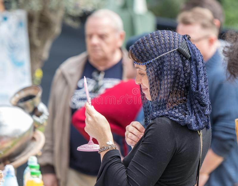 Deltagaren av festivalen i dräkten av en medeltida dam försöker på en kedja och ser i en spegel på den Purim festivalintelligense arkivbilder