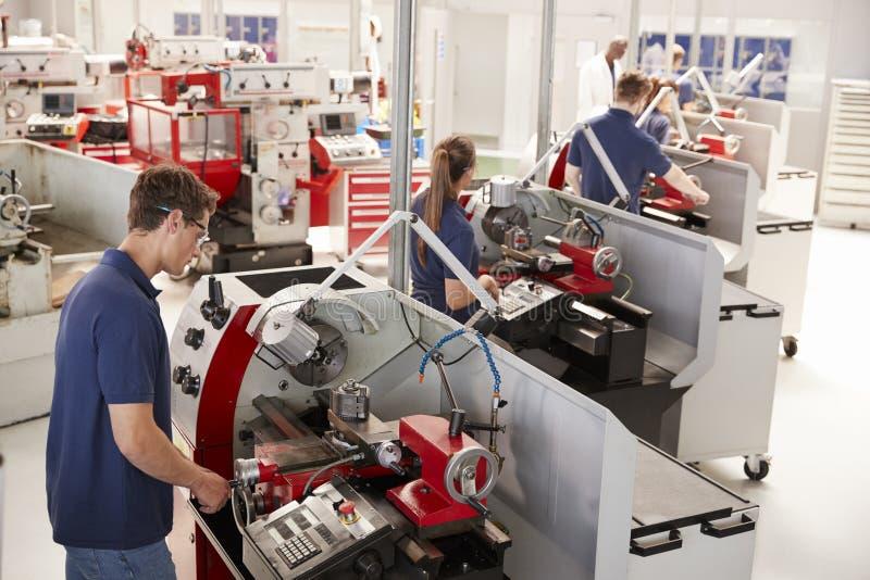 Deltagaren i utbildning iscensätter fungeringsutrustning i en liten fabrik royaltyfria bilder