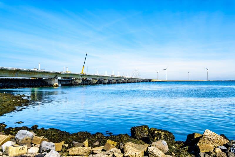 Deltan arbetar turbiner för barriären och för vind för stormsvallvåg på Oosterschelden som beskådas från den Neeltje Jans ön royaltyfri bild