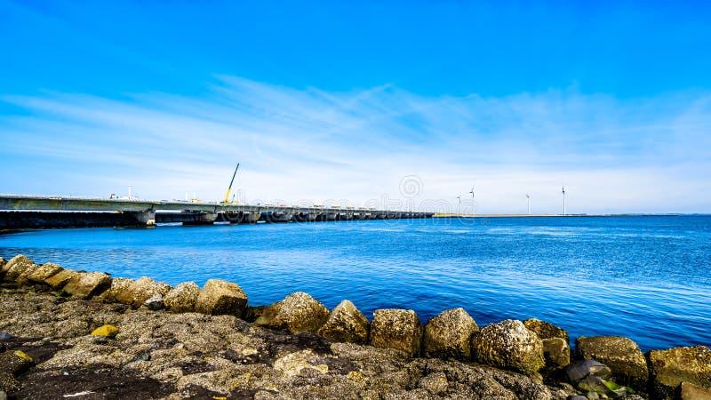 Deltan arbetar turbiner för barriären och för vind för stormsvallvåg på Oosterschelden som beskådas från den Neeltje Jans ön royaltyfria foton