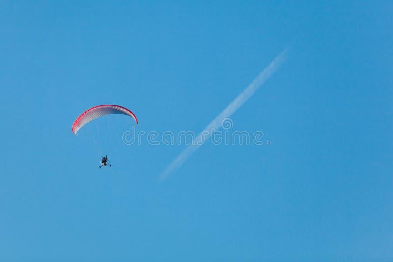 Deltaplano e traccia di condensazione su un cielo fotografia stock