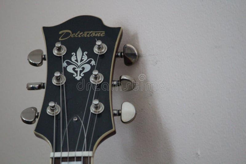 Deltatone gitarrsammanträde mot väggen fotografering för bildbyråer