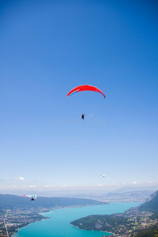 Deltavlieger en Glijscherm die over Annecy Meer door Berglandschap en Steden vliegen royalty-vrije stock afbeelding
