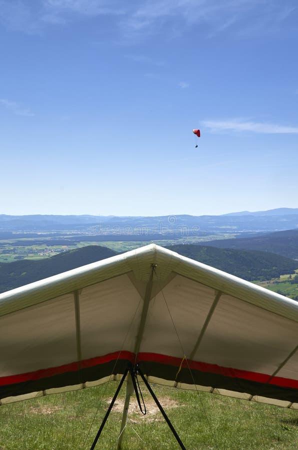 Deltavlieger op grond en een glijscherm in de lucht stock foto