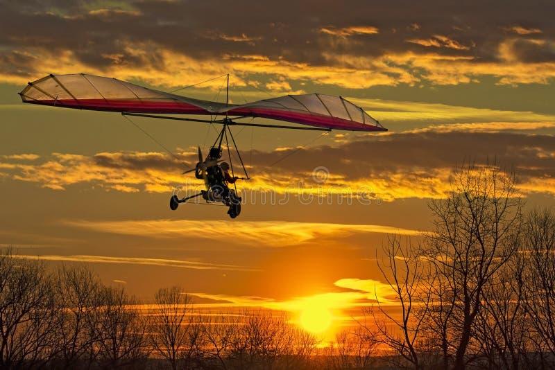 Deltavliegervlieg in de zonsondergang stock foto