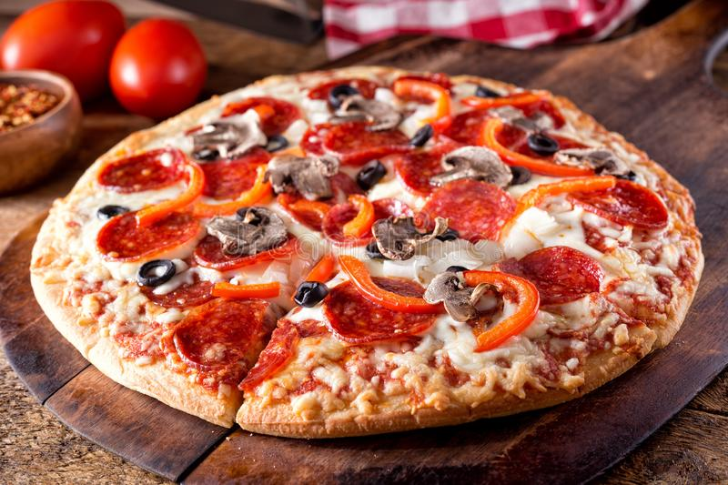 Deluxe Brick Oven Baked Pizza. A brick oven baked pizza deluxe with pepperoni, mushroom, red pepper, onion and black olives or a rustic wood board stock images