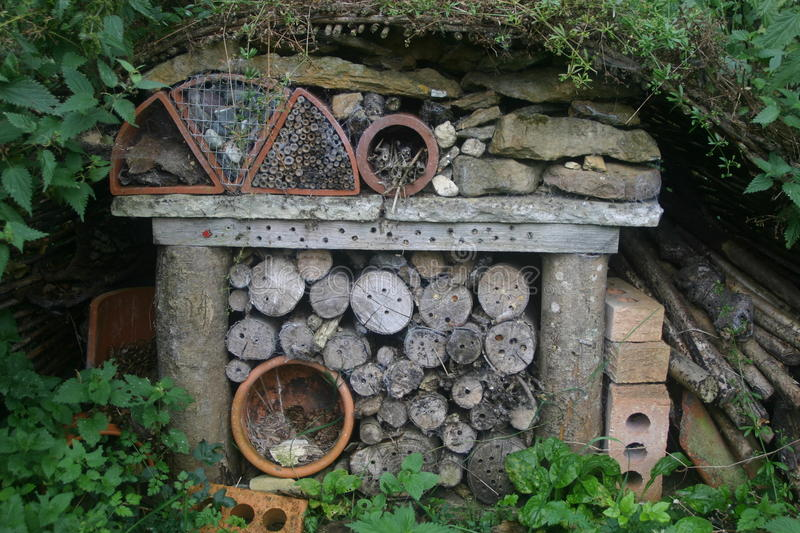Bug hotel. Made from logs, bricks, flower pots, stones and dead wood with trees as the background royalty free stock photography