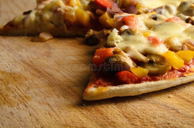 Delvis äten vegetarisk pizza på skärbräda royaltyfri foto