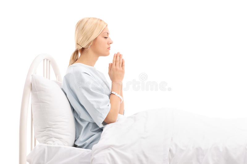 Female patient lying in a hospital bed and praying stock images