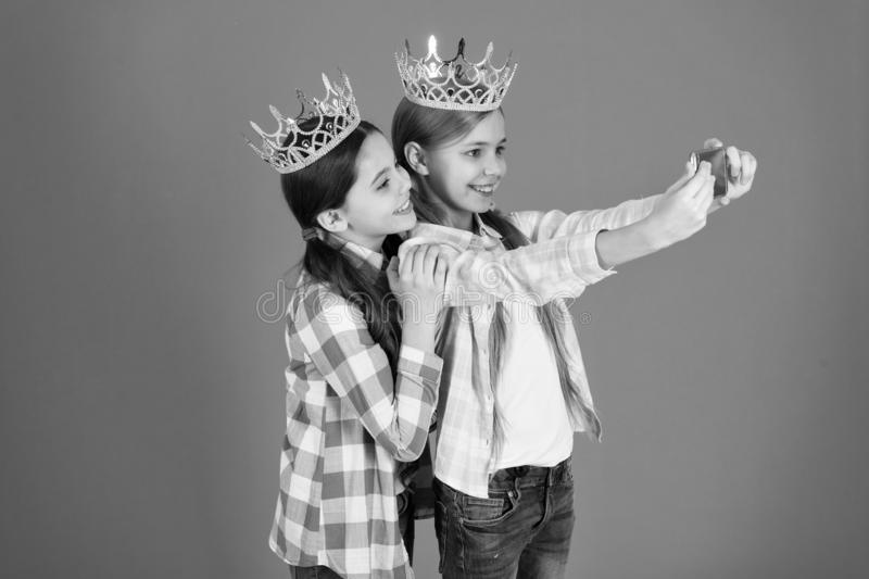 Demand more attention. Kids wear golden crowns symbol princess. Warning signs of spoiled child. Avoid raising spoiled. Kids. Girls taking selfie photo stock photo