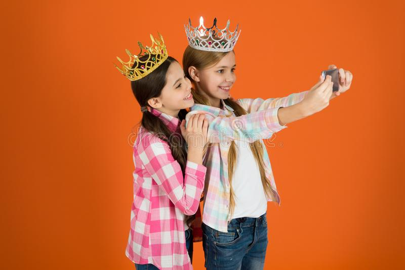 Demand more attention. Kids wear golden crowns symbol princess. Warning signs of spoiled child. Avoid raising spoiled. Kids. Girls taking selfie photo stock photos
