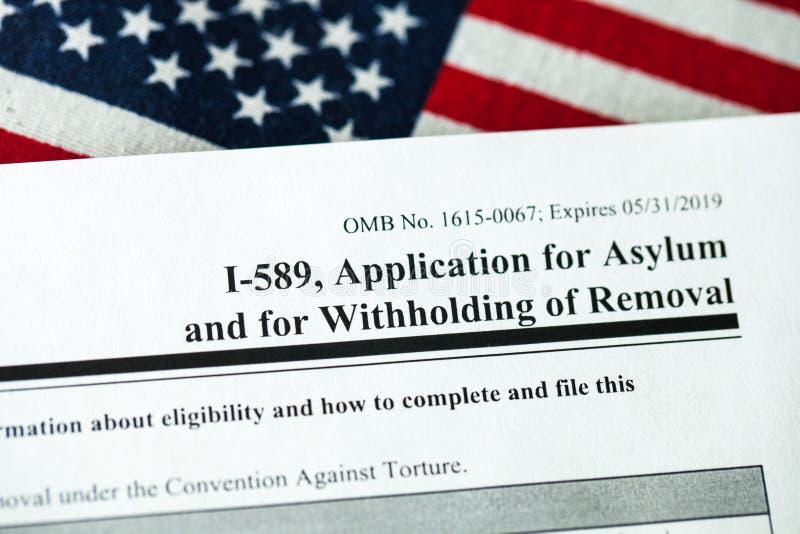 Demande d'asile au concept des Etats-Unis avec le formulaire de demande et le drapeau des Etats-Unis à l'arrière-plan photographie stock libre de droits