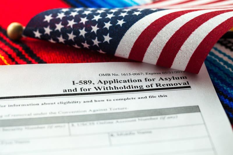 Demande d'asile au concept des Etats-Unis avec le formulaire de demande et le drapeau des Etats-Unis sur le serape mexicain photos libres de droits