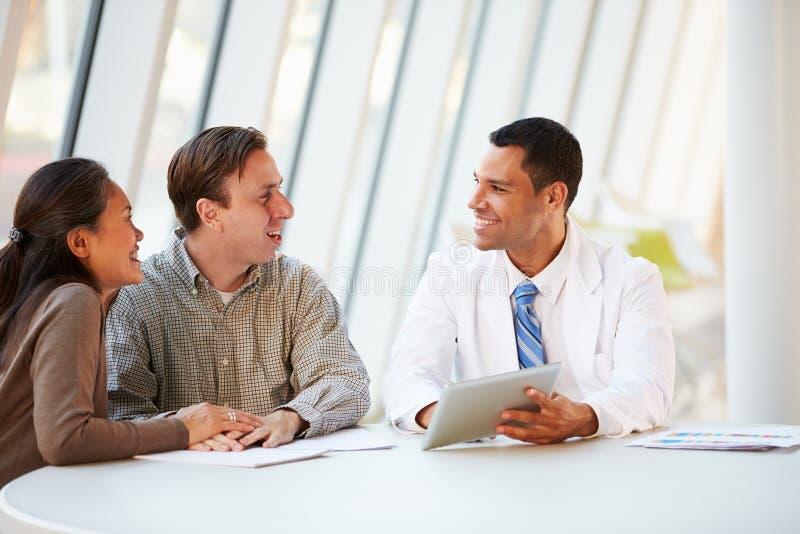 Demande de règlement de docteur Using Tablet Computer Discussing avec des patients photos libres de droits