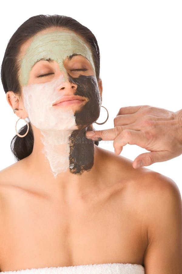 Demande de règlement de station thermale - colorez le masque facial sur le femme ethnique photographie stock libre de droits