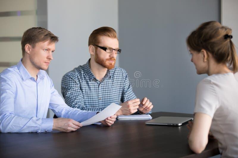 Demandeur féminin de écoute de mâle d'équipe sérieuse d'heure à l'entrevue d'emploi images stock