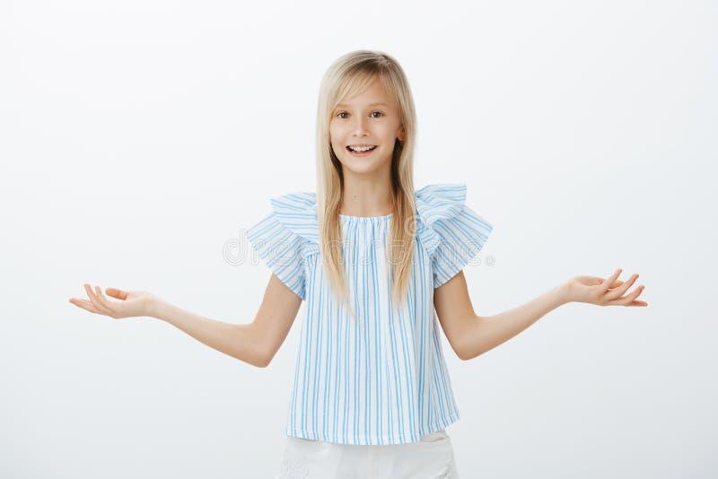 Demasiadas opciones para un niño Retrato de la muchacha rubia joven atractiva confusa desorientada en la blusa azul, palma de ext fotos de archivo