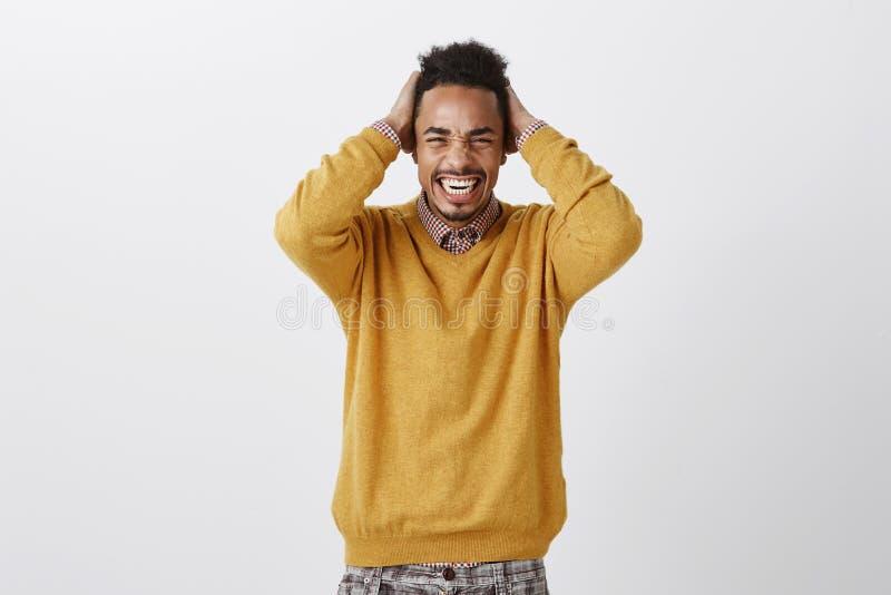 Demasiado dolor para una cabeza Retrato del afroamericano atractivo incómodo descontentado en la tenencia amarilla del suéter fotografía de archivo