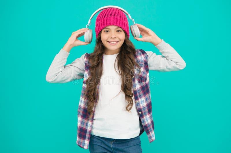 Demasiado fuerte adolescente escucha música en los auriculares libro de audio para niños pequeños autoeducación en línea pelo lar foto de archivo libre de regalías