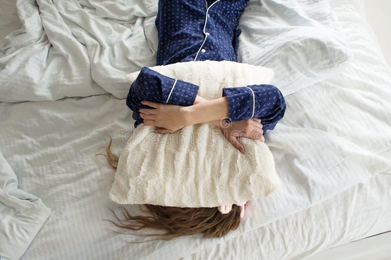 Demasiado perezoso salir de cama, una mujer cubre su cara con una almohada foto de archivo libre de regalías