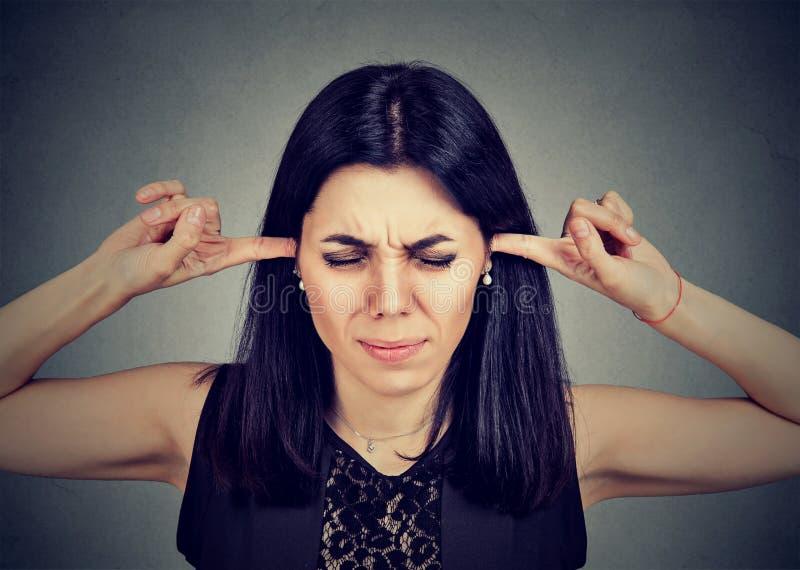 Demasiado ruido Mujer joven enojada que tapa sus oídos con los fingeres imagen de archivo libre de regalías
