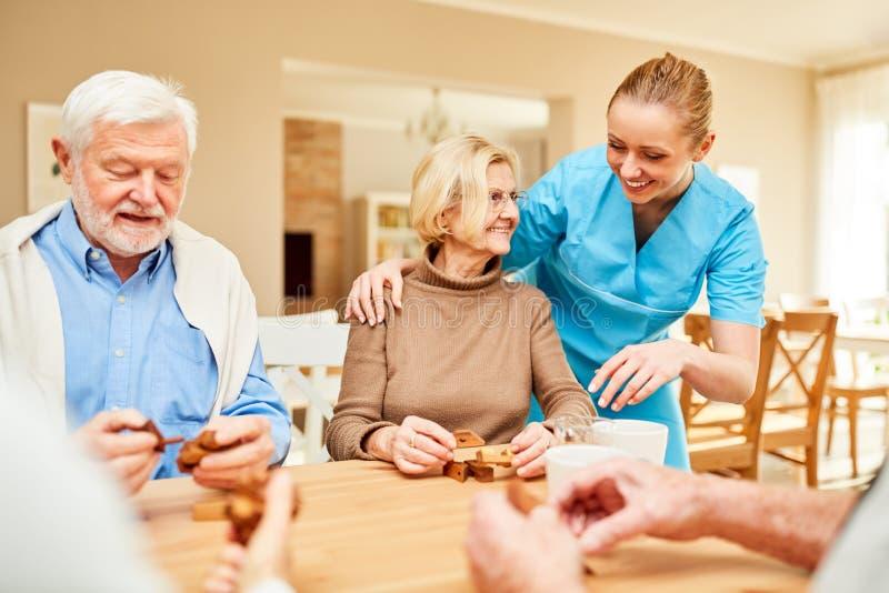 Dementa pensionärer som spelar träpusselleken av patiens royaltyfri fotografi