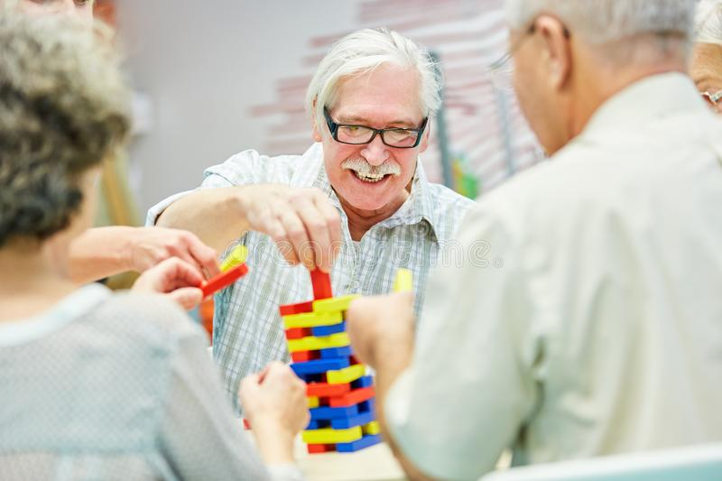 Dementia group in retirement home plays with building blocks royalty free stock images