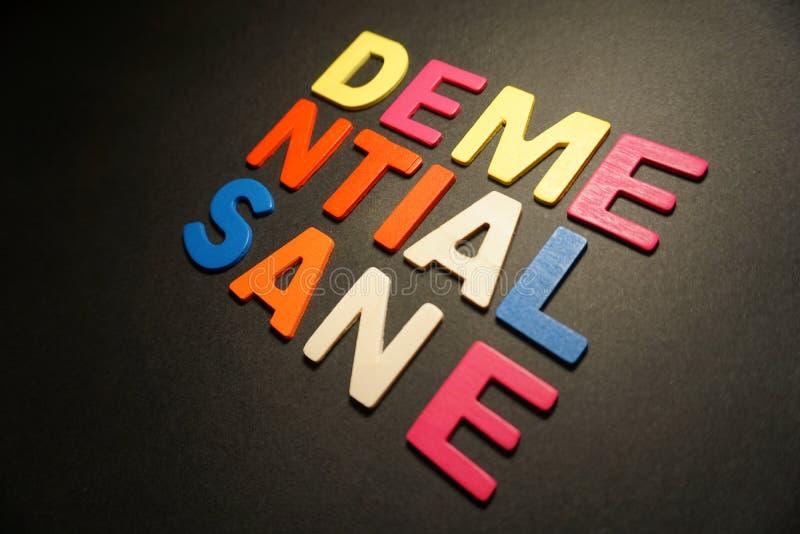 Demential-Sane. Demantial sane wood color letters on black background stock images