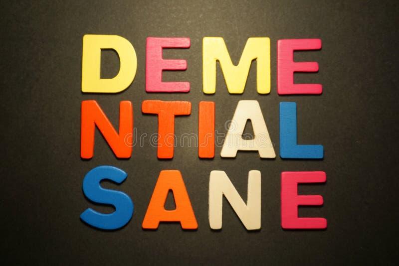 Demential-Sane. Demantial sane wood color letters on black background royalty free stock image