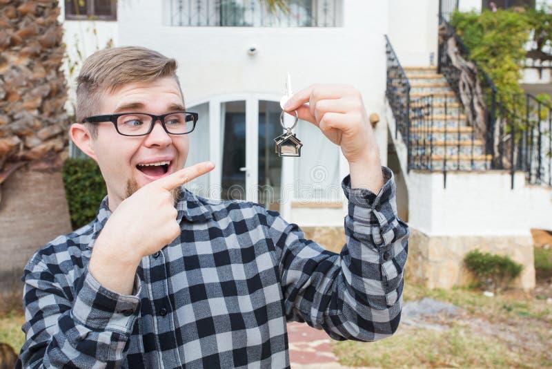 Demeure, maison de achat, immobiliers et concept de propriété - homme bel montrant sa clé à la nouvelle maison photographie stock