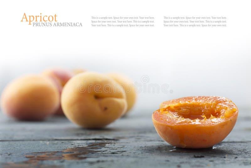 Demi abricot et fruits brouillés derrière sur le vieux bois gris images libres de droits